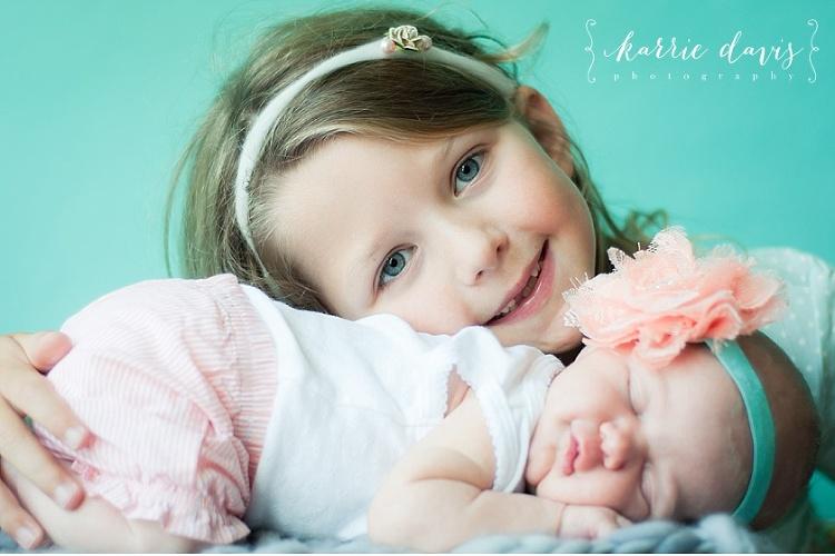 newborn baby girl photo shoot with her big sister. love the cute headband
